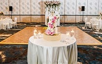 A cake decorated with several large roses on a table in the middle of a room also featuring a dance floor