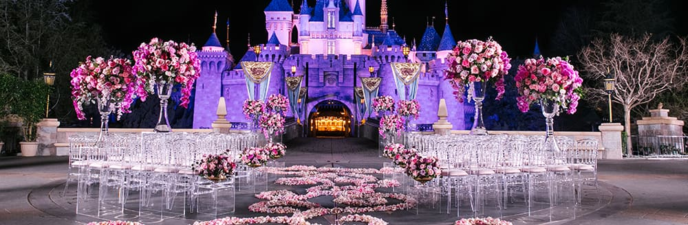 Chairs, flowers and an aisle of petals ready for a wedding ceremony in front of Sleeping Beauty Castle