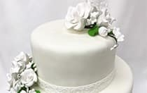 A 2 tier wedding cake topped with flowers