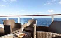 An outdoor patio with chairs and a table overlooks the ocean