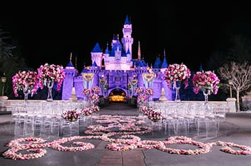 A wedding venue set up in front of Cinderella Castle at night