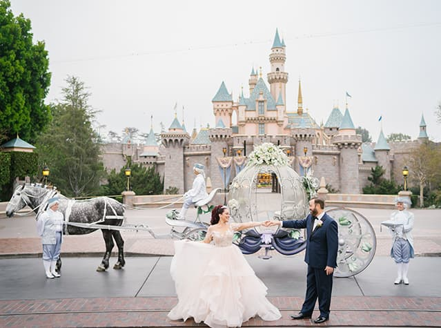 A bride and groom holding hands in front of Cinderella's Crystal Coach