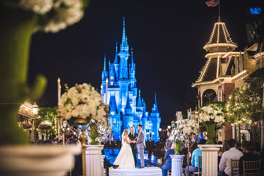 A couple and an officiant stand in front of Cinderella Castle as they get married on Main Street, USA which is decorated with columns of floral bouquets and has a group of seated Guests