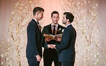 Two men getting married near small lit trees