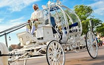 A man driving Cinderella's Coach outside