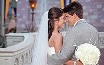 A bride and groom cuddle in front of Cinderella Castle