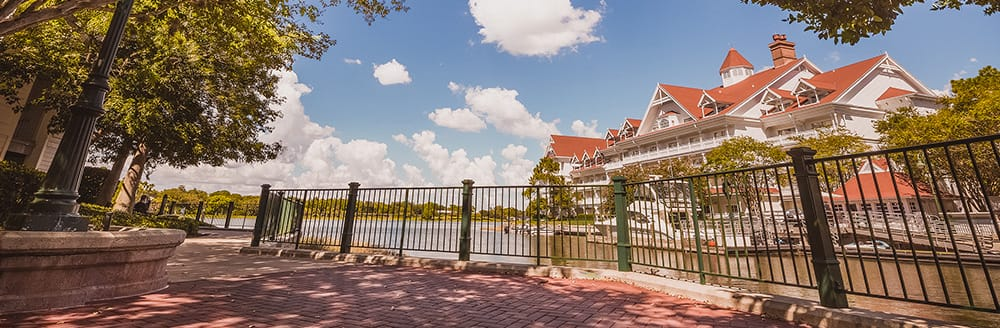 A shady brick path with a cast iron guardrail and old fashioned streetlamps looks out to the Seven Seas Lagoon and Disney's Grand Floridian Resort & Spa