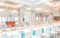 Several chairs around a long table decorated with seashells and lanterns under ornate hanging decorations