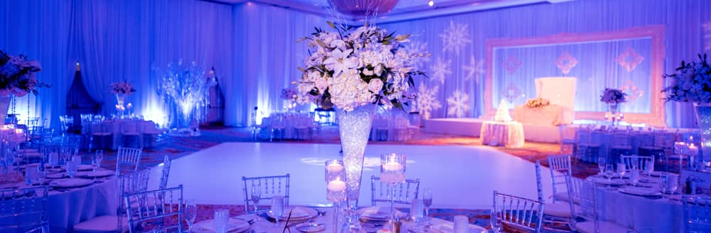 Large snowflakes are projected on the walls and tall floral arrangements rest on tables in the middle of a ballroom