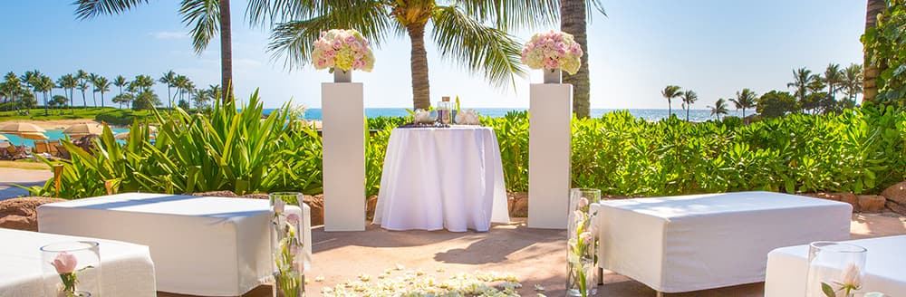 In a beachfront garden at Aulani Resort, banquettes and glass vases are arranged in front of an altar that is flanked by pillars topped with rose bouquets