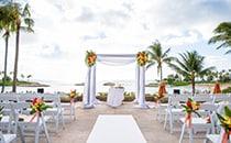Floral arrangements adorn a wedding altar on a patio overlooking the ocean