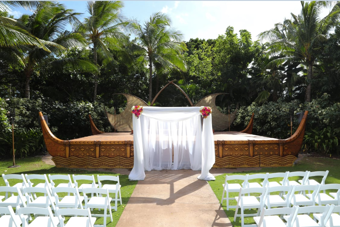 An altar arranged in front of a stage surrounded by lush trees