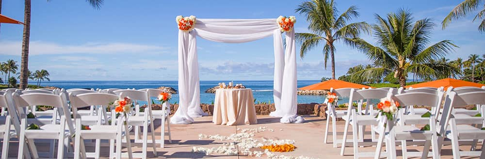 A wedding altar and chairs scattered with flower petals for a ceremony by the sea