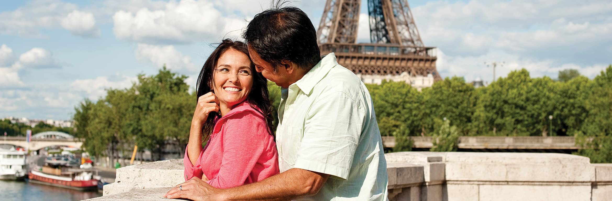 A man and a woman cuddle in front of France's Eiffel Tower in Paris