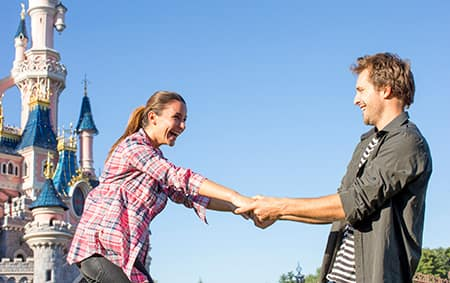 A man pulls a laughing woman towards him by Sleeping Beauty Castle