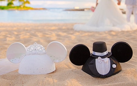 A Minnie ear hat decorated with a crown and veil next to a Mickey ear hat decorated with a top hat and tuxedo