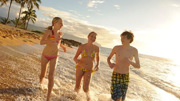 Three teens running on the beach in the mid-afternoon sun