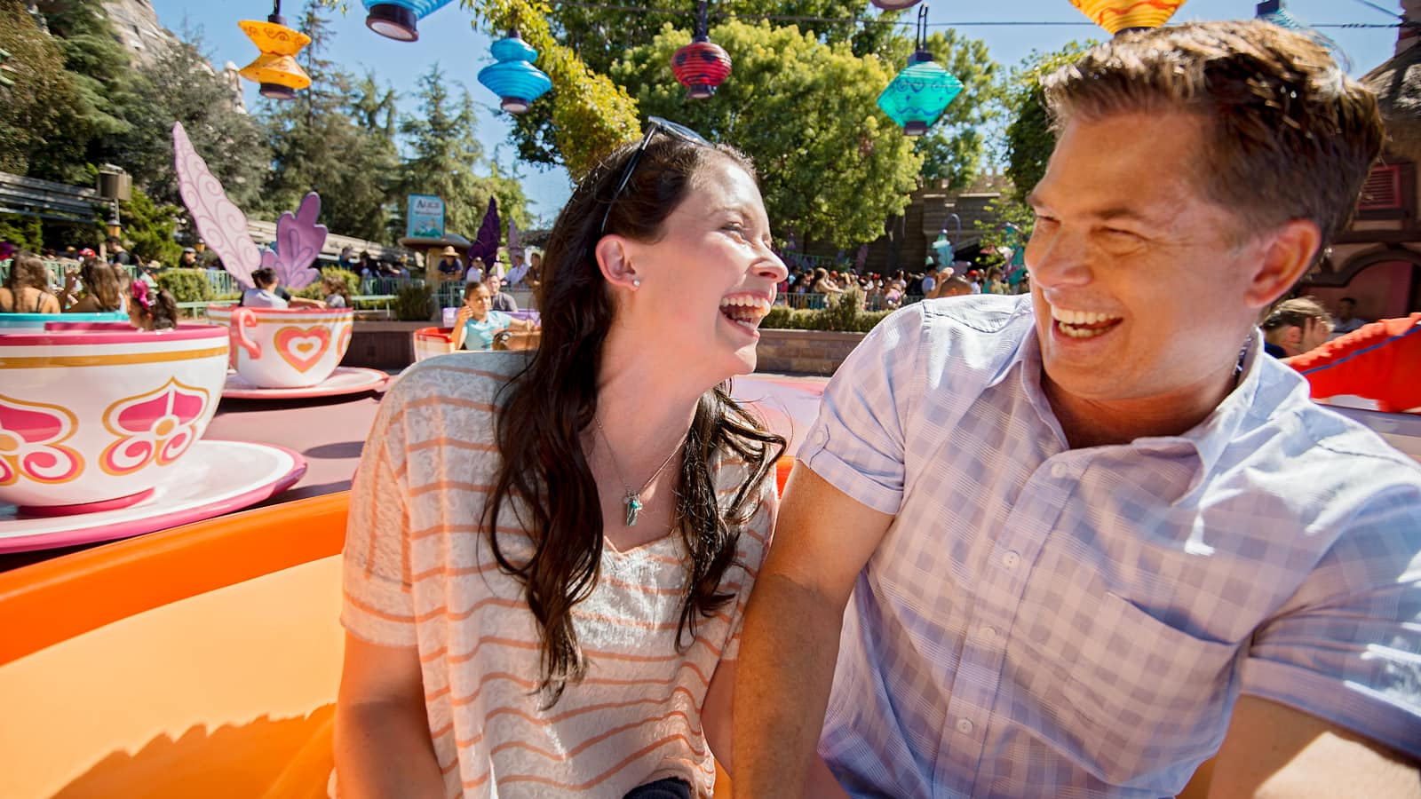 A man and a woman smile as they spin around in tea cups at the Mad Tea Party attraction