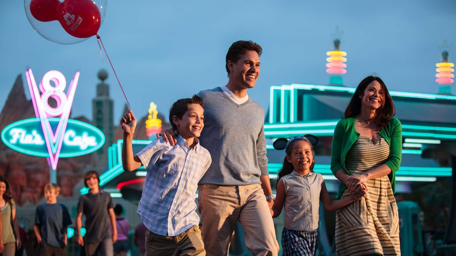 A family of 4 walks in front of building with neon sign that says 'Flo's Cafe' at dusk