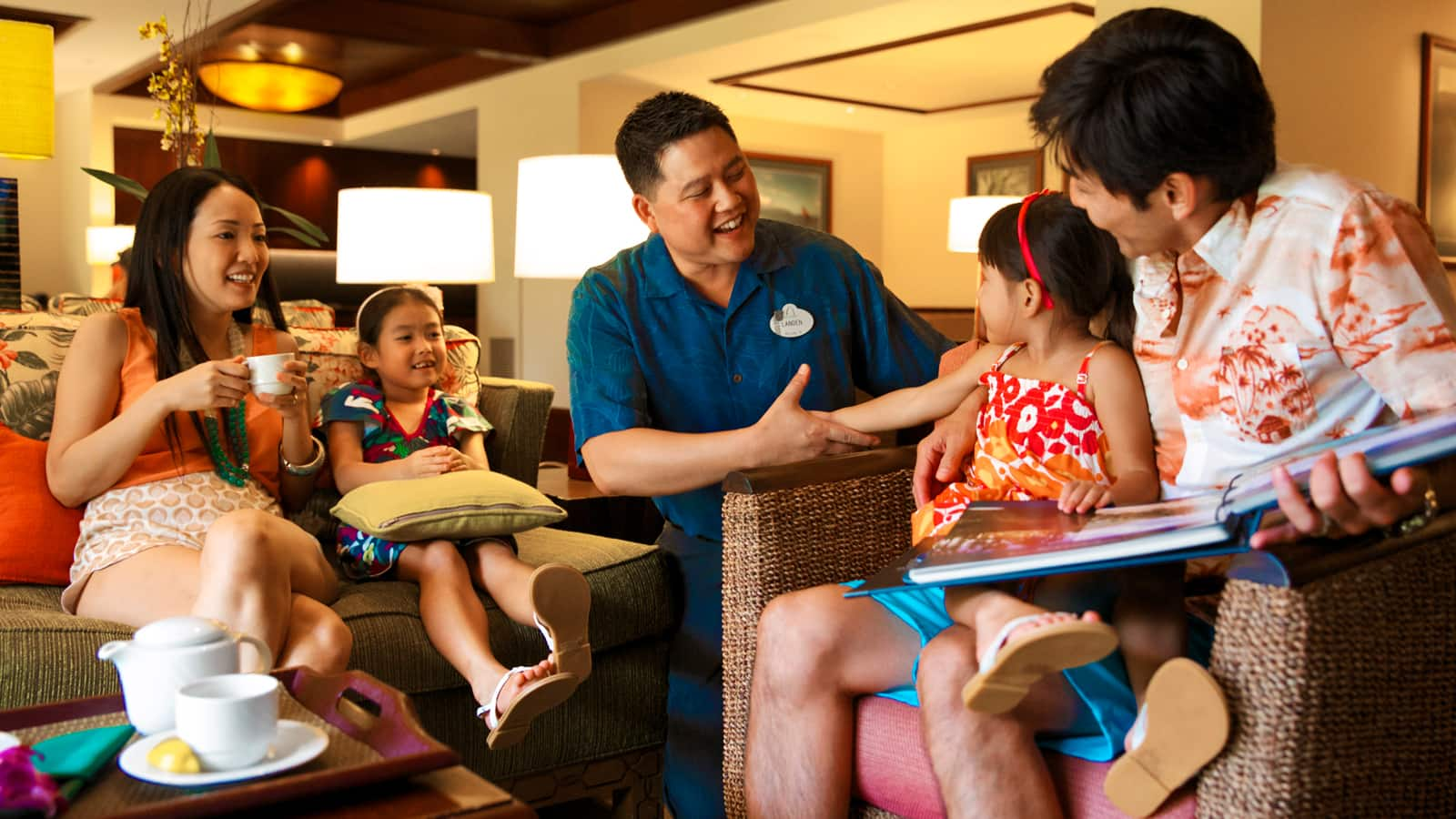 A Disney Cast Member greets a family of 4 seated in a small lounge area