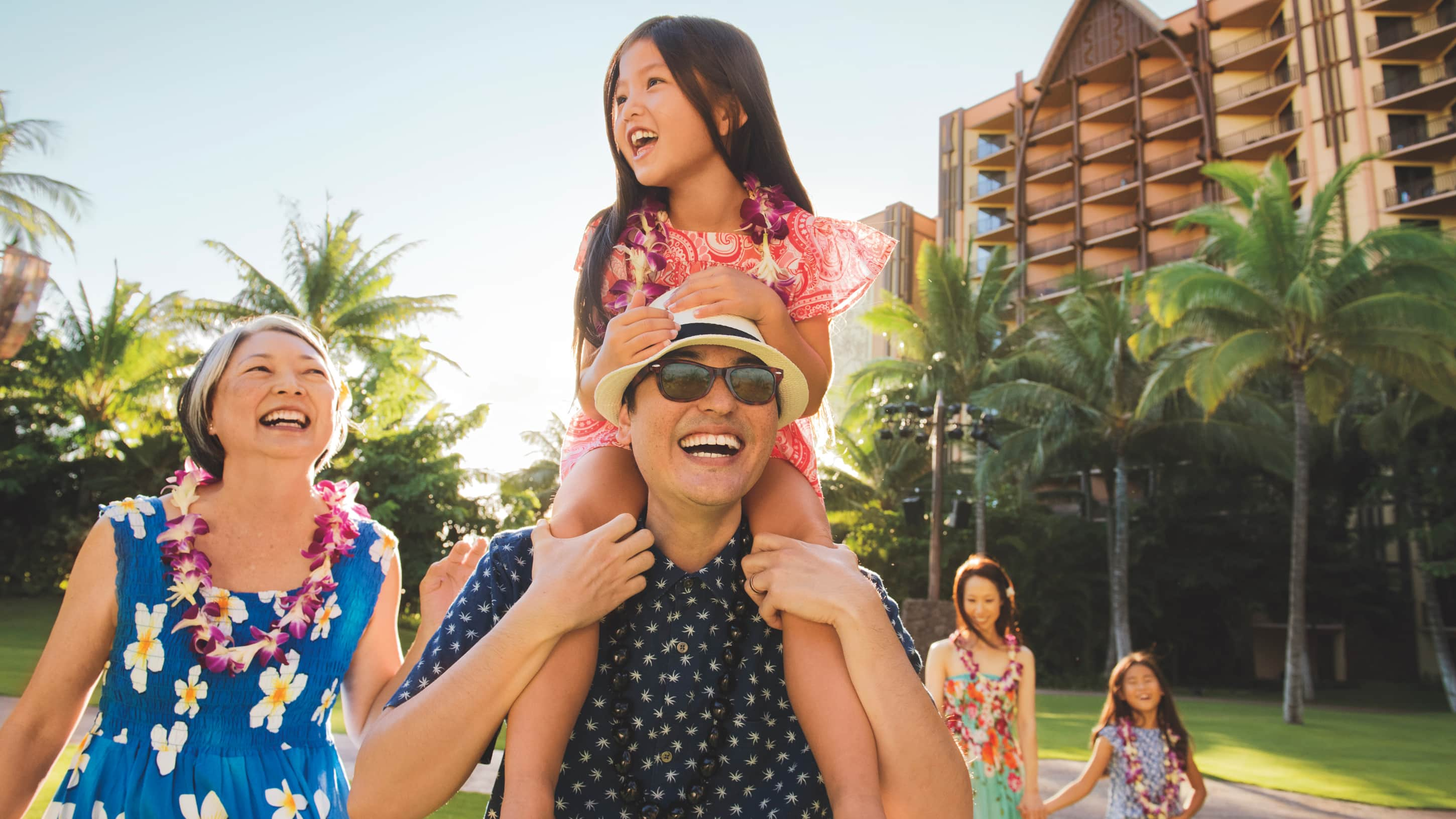 3 children, their mother, father and grandmother walking outdoors at Aulani Resort