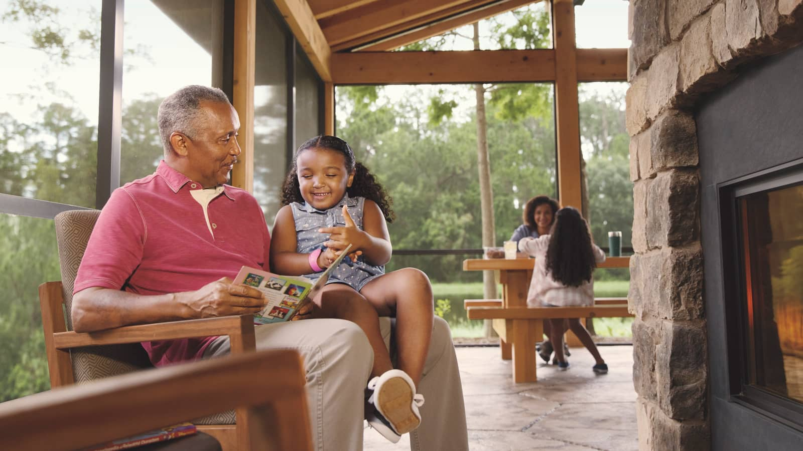 A grandfather, his daughter and 2 granddaughters relax in an outdoor living area