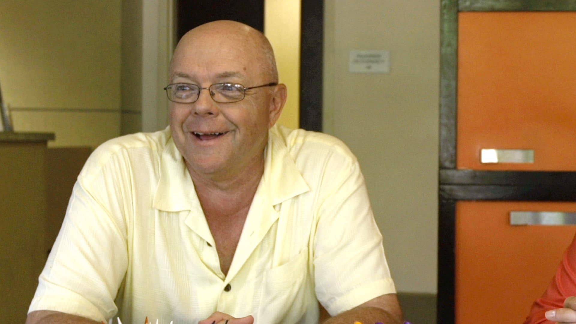 A man with a wide smile wearing a buttoned up short sleeve shirt sits with his hands clasped