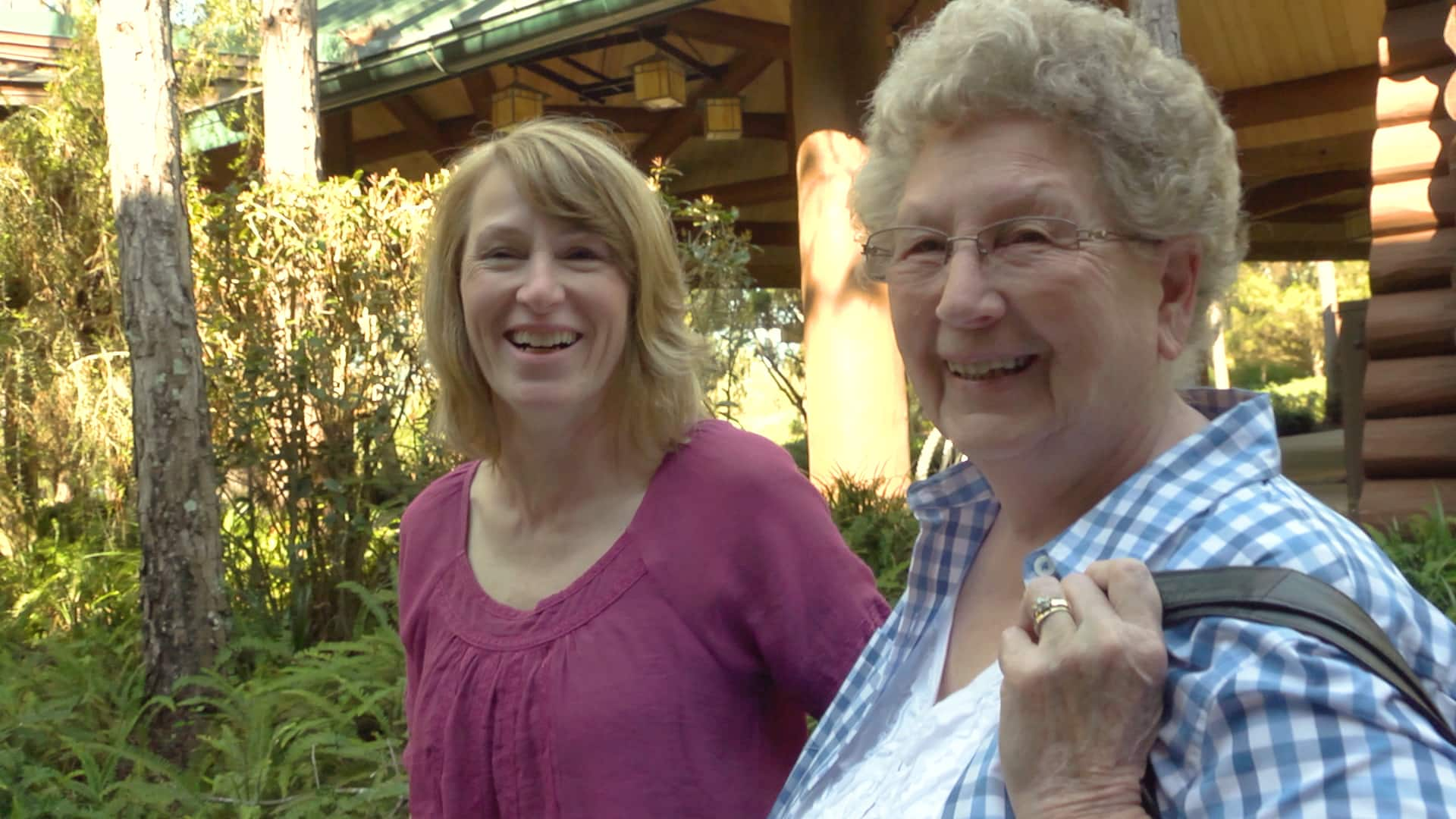 A woman and her mother smile as they stand in front of a log cabin style awning