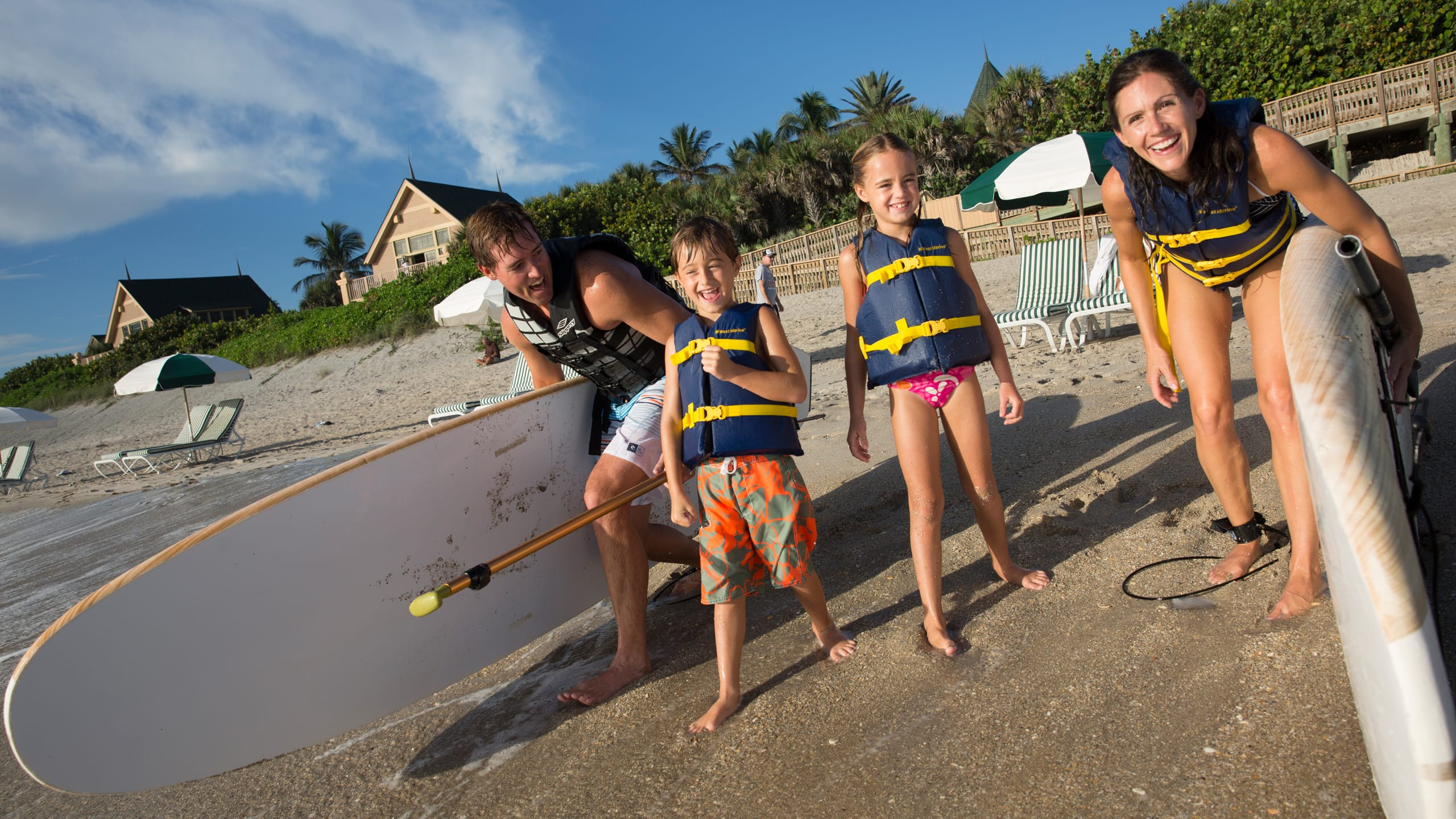 A mother, father, son and daughter with paddleboards on a beach