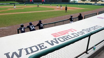 "Varios jugadores en el campo de béisbol, junto a una pancarta que dice ""ESPN Wide World of Sports Complex""."