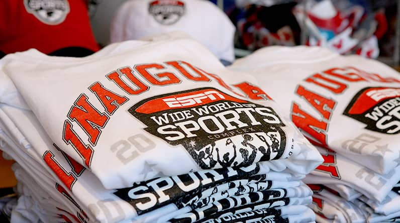 Two stacks of folded ESPN Wide World of Sports t-shirts