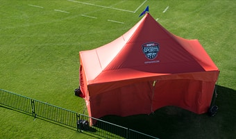 A large tent near the corner of a soccer field