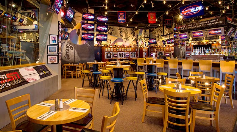 Dining tables surrounded by TVs on the main floor of ESPN Club at Disney's BoardWalk