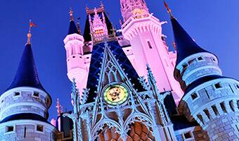 The spires of Cinderella Castle awash in 2 different colors at night