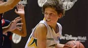 A boy looks to pass the basketball while being guard by 2 opponents