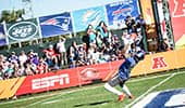 A football player catches a ball on a field in front of many spectators