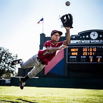 A youth baseball player dives for a baseball in the outfield near a scoreboard that reads 'ESPN Wide World of Sports