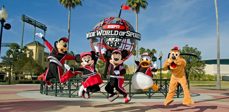 Goofy, Minnie Mouse, Mickey Mouse, Donald Duck and Pluto, all in athletic outfits, leap into the air in front of a large globe that reads 'ESPN Wide World of Sports Complex'