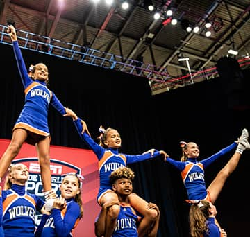 Eight girls from the Wolves cheer team in a formation where 5 girls hold 3 girls on their shoulders in front of an ESPN Wide World of Sports banner