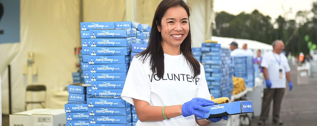 While holding out a boxed meal, a smiling volunteer stands outside a food tent stacked with meal boxes