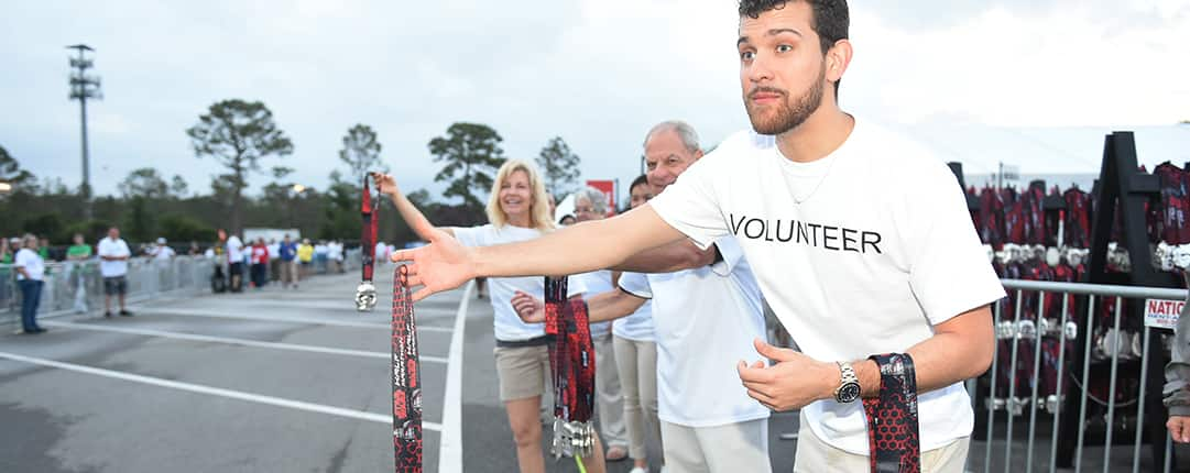 A row of volunteers pass out Star Wars lanyards to runners along the race route with bystanders in the background