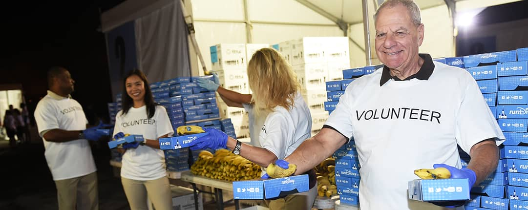 Standing by tables stacked with boxed meals and bananas, 4 volunteers prepare to hand out food to passing race runners