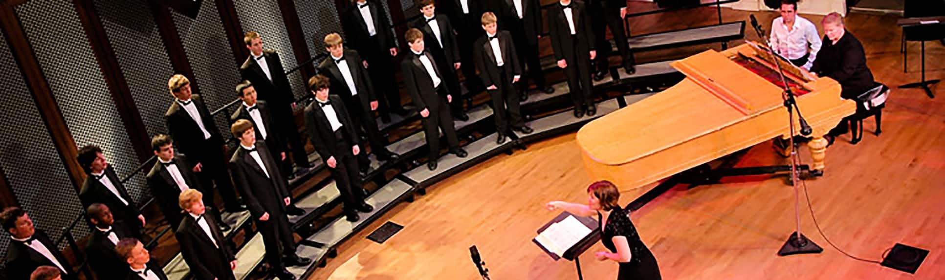 A choir of young adults dressed in tuxedos performing with piano accompaniment and a conductor