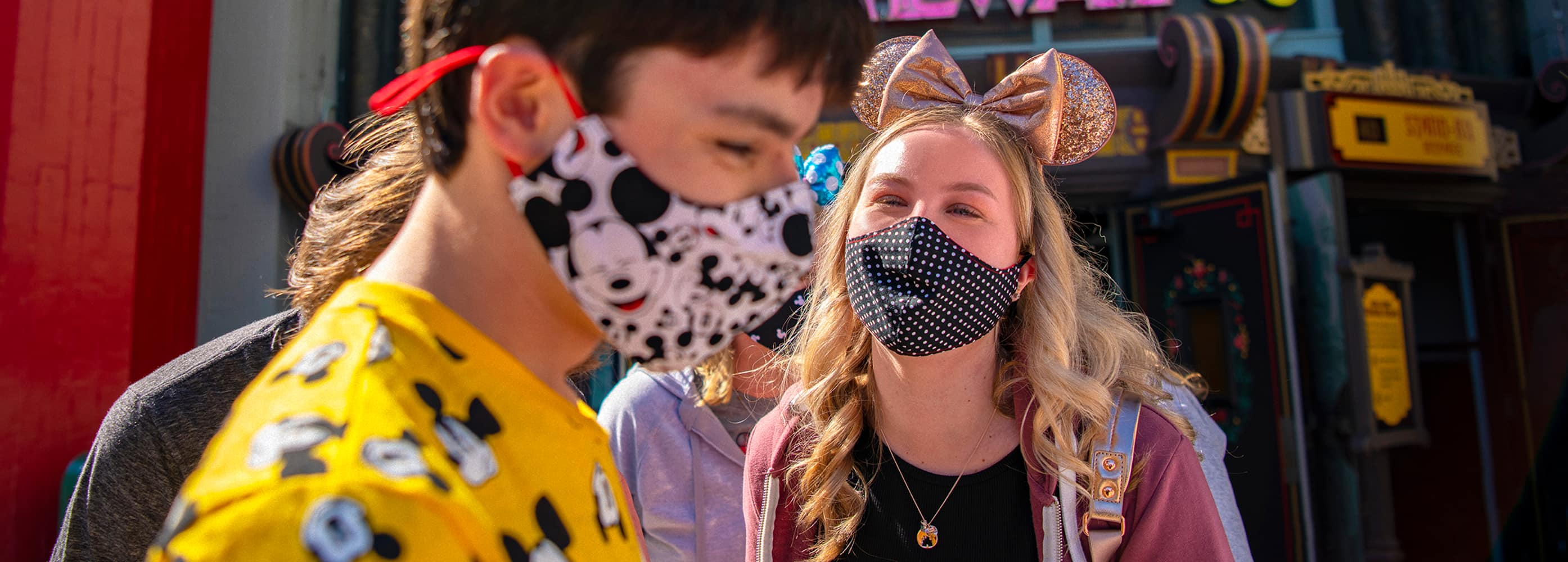 A teen boy wearing a Mickey Mouse mask and shirt talks with a teen girl wearing a mask and Minnie Mouse ear headband with a bow in front of Mickey and Minnie's Runaway Railway at Disney's Hollywood Studios