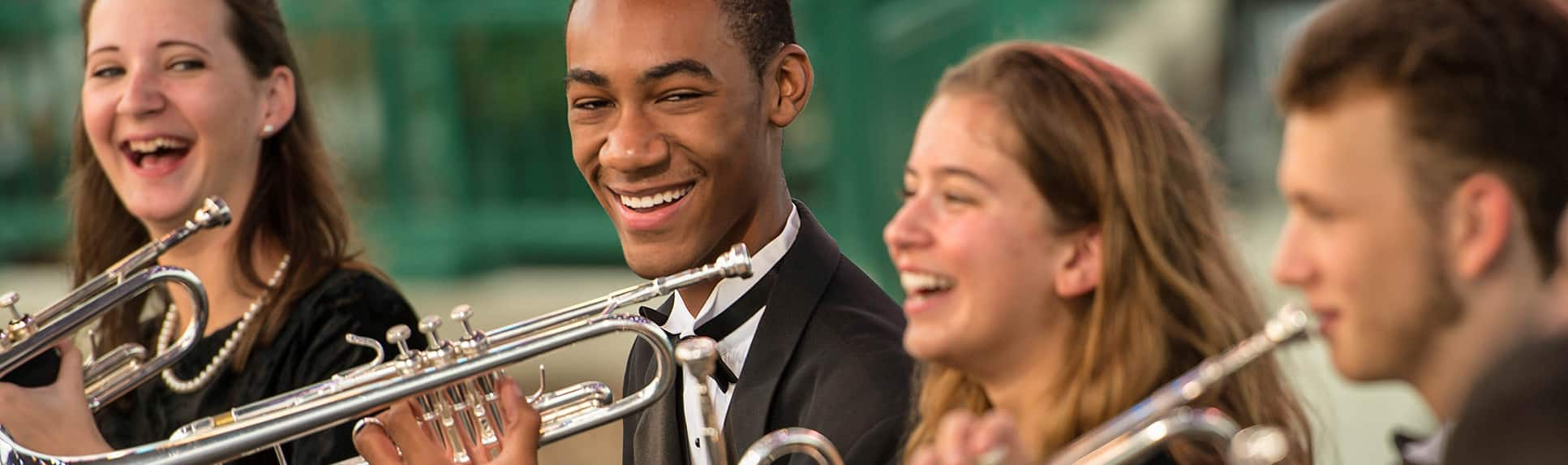 Two girls and two boys in the trumpet section of a school band smile broadly during a concert