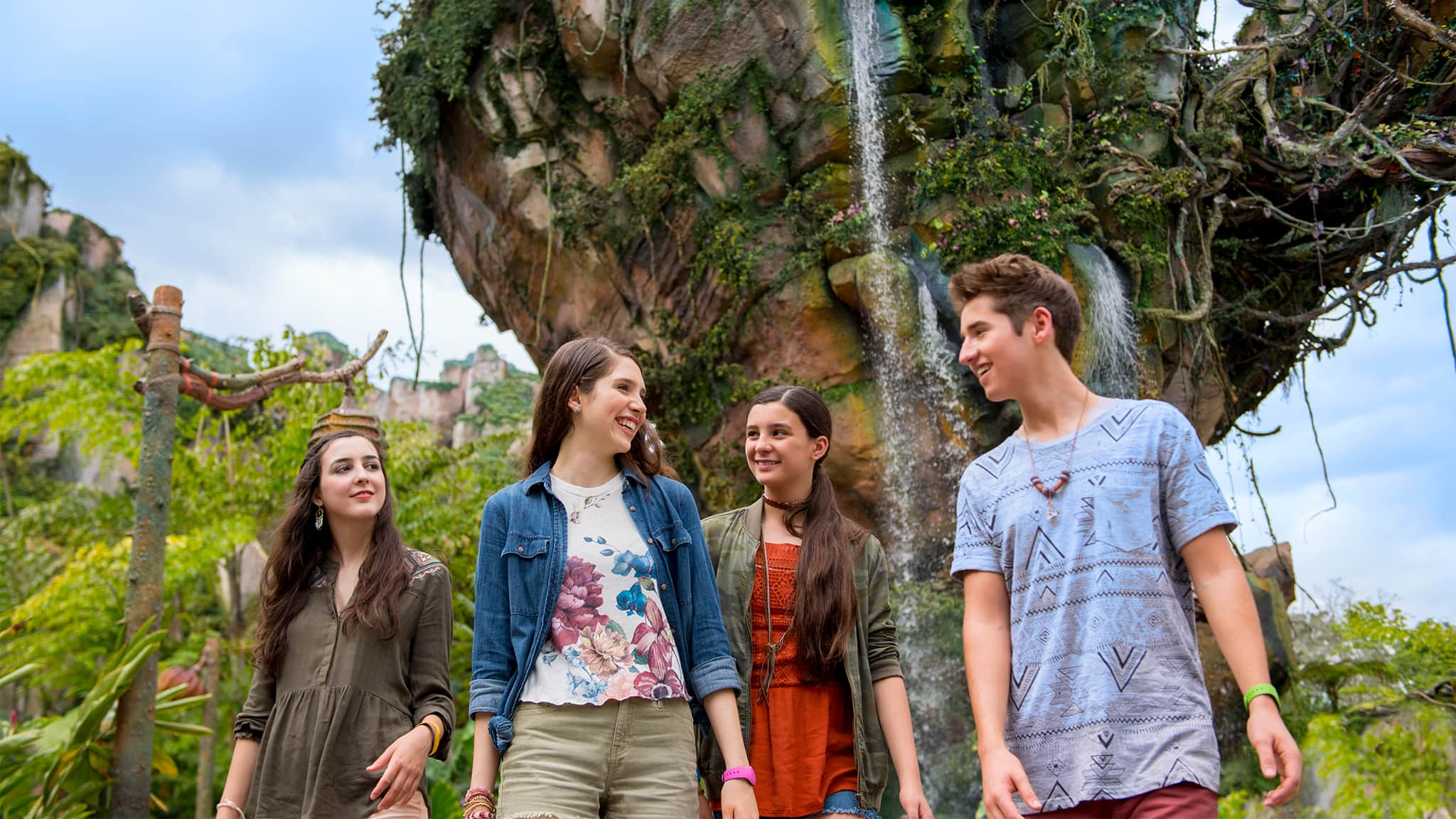Three young women and a young man in front of a tall rock formation streaming with cascades of water