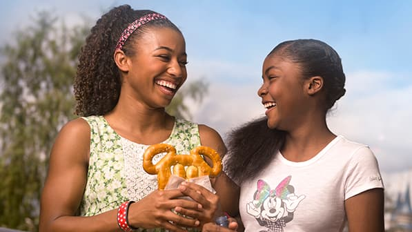A woman holding a Mickey pretzel smiles with her daughter