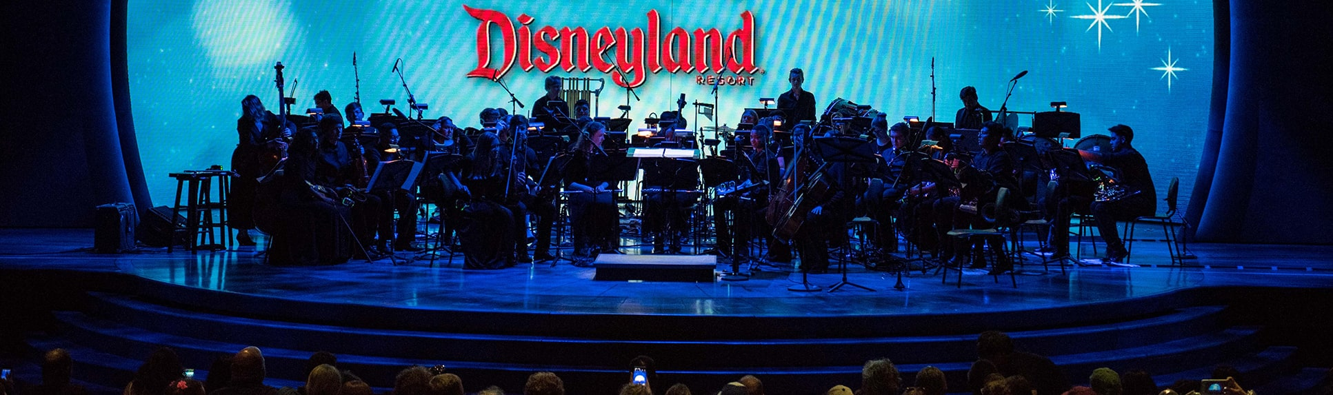 An orchestra on stage in front of a circular video screen backdrop reading Disney Performing Arts Conservatory Disneyland