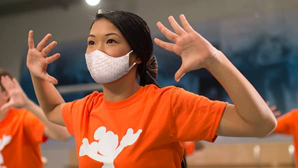 A teen girl wearing a mask and Mickey Mouse t shirt stands with her hands in the air and fingers spread wide