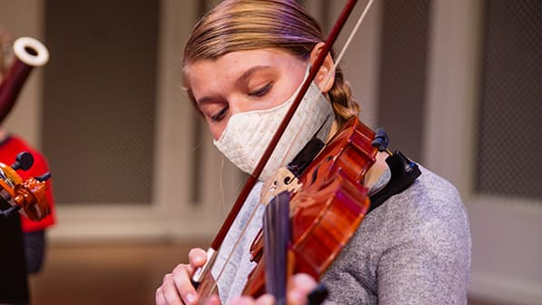 A young woman in a mask plays a violin